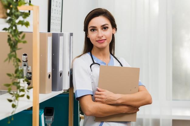Portrait of female doctor holding a folder Free Photo