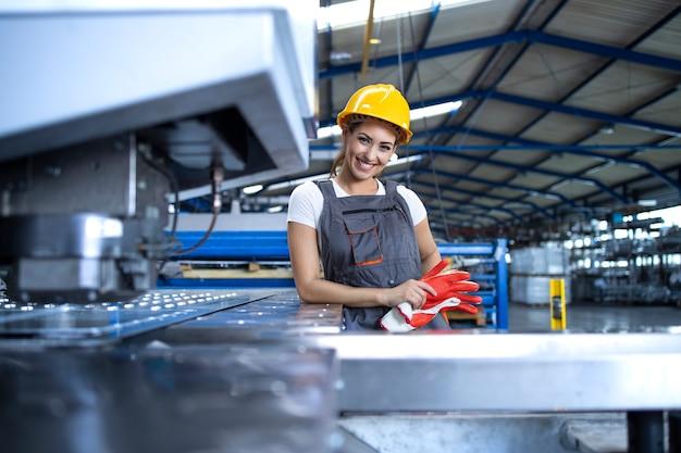 Ritratto di operaio femminile in uniforme protettiva e hardhat in piedi dalla macchina industriale alla linea di produzione Foto Gratuite