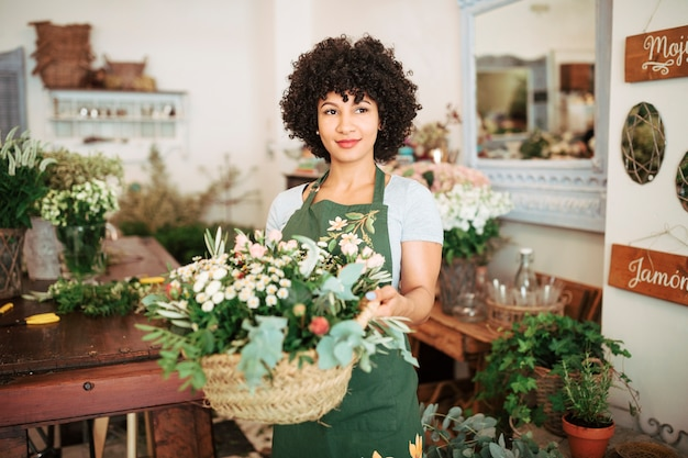 Portrait of a female florist holding basket of fresh flowers Premium Photo