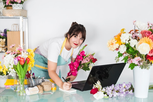 Portrait of a female florist with flowers writing on notepad Free Photo