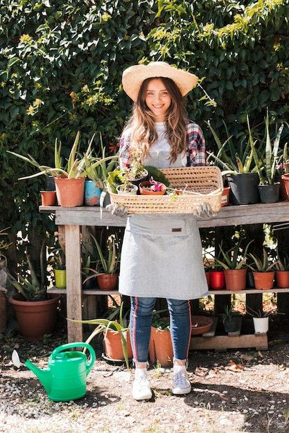 Portrait of a female gardener wearing hat holding the selected potted plant in the basket Free Photo
