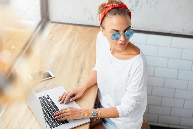 Ritratto di donna manager lavora su business plan al computer portatile, passa in rassegna le informazioni, guarda premurosamente da parte, circondato da moderni gadget elettronici. l'editor della donna controlla il contenuto sul sito web Foto Gratuite