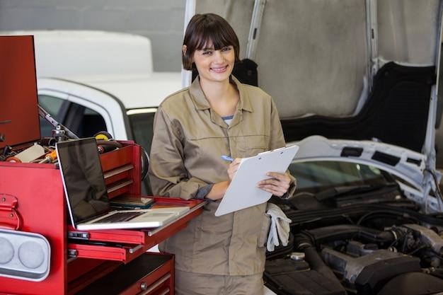 Portrait of female mechanic preparing a check list Free Photo