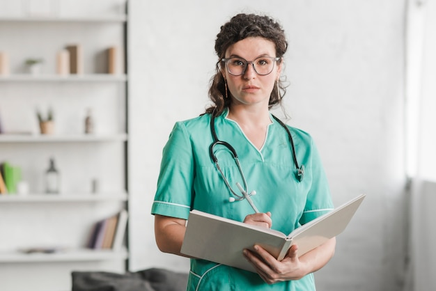 Portrait of female nurse holding book and pen Free Photo