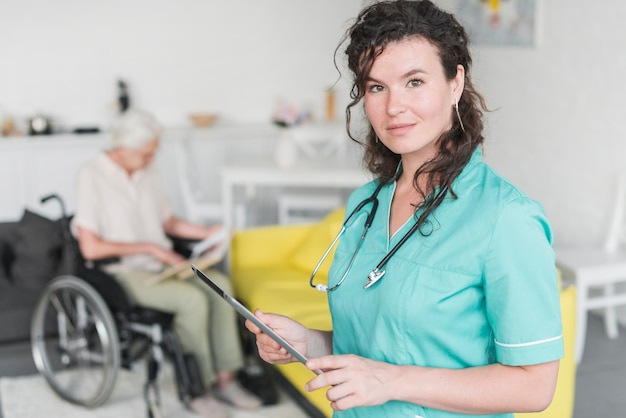 Portrait of female nurse holding digital tablet standing in front of senior patient on wheelchair Free Photo