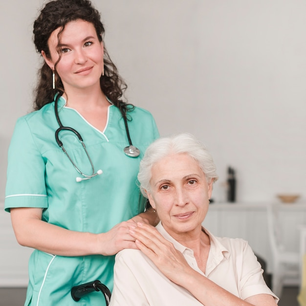 Portrait of female nurse with her senior patient sitting on wheel chair Free Photo