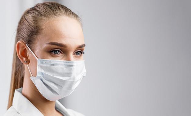 Ritratto di ricercatore femminile con maschera medica e copia spazio Foto Gratuite