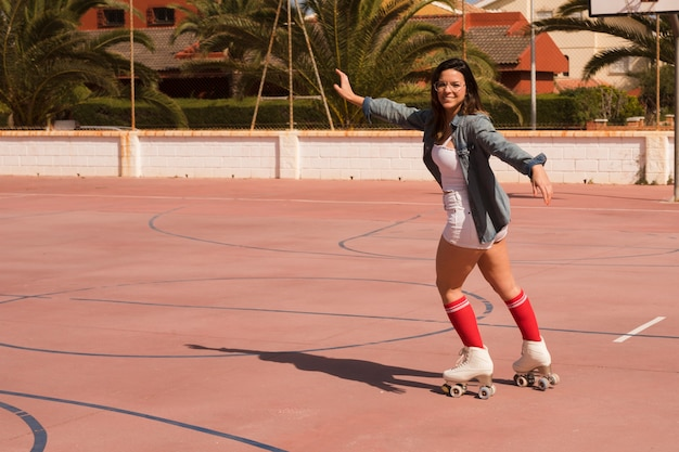 Portrait of a female skater outstretching her arms skating on an outdoor court Free Photo