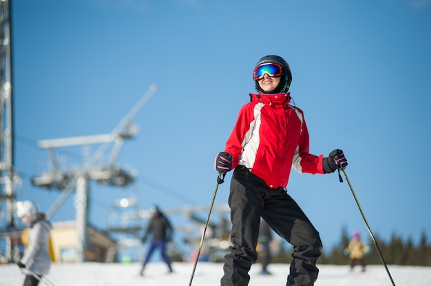 Portrait of female skier standing with skis on mountain top at a winter resort in sunny day Premium Photo