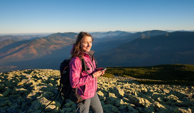 Portrait of female standing on rocky top of the mountain Premium Photo