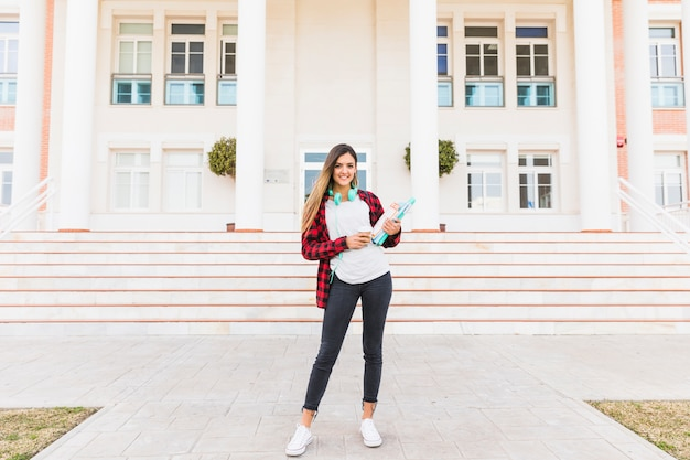 Portrait of a female student holding books in hand standing in front of college Free Photo