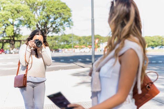 Portrait of a female tourist taking photograph of her female friend from camera Free Photo