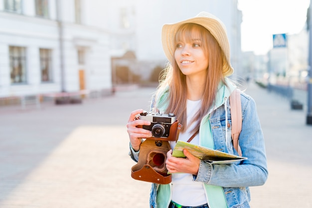 Portrait of a female traveler in city holding vintage camera and map in hand looking away Free Photo