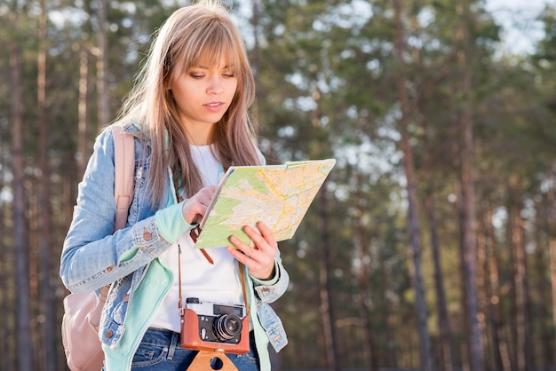 Portrait of a female traveler searching on map in the forest Free Photo