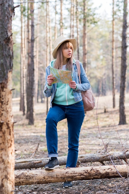Portrait of a female traveler standing in the forest with map Free Photo