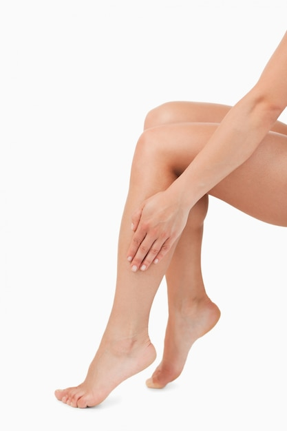Portrait of a feminine hand touching legs Premium Photo