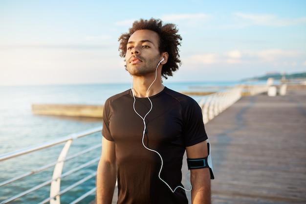 Portrait of fit dark-skinned muscular man runner with bushy hairstyle looking concentrated in black sport clothing wearing white earphones. Free Photo