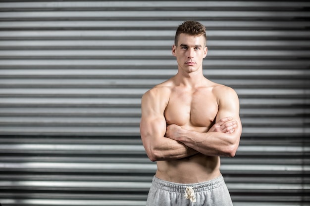 Portrait of fit man with crossed arms at crossfit gym Premium Photo