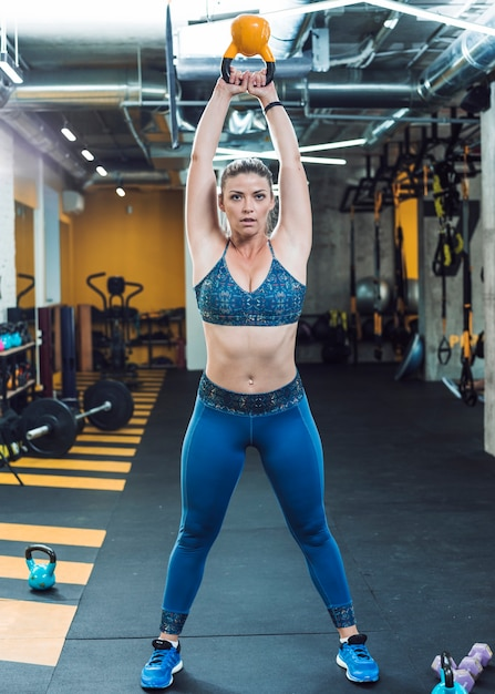 Portrait of a fit woman doing exercise with kettle ball Free Photo