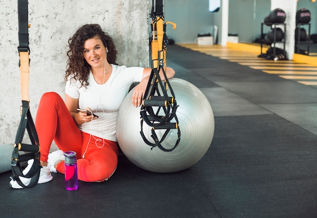 Portrait of a fit woman using mobile phone in fitness club Free Photo