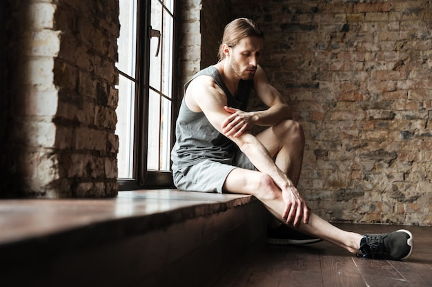 Ritratto di un uomo di forma fisica che soffre di un dolore alla gamba Foto Gratuite