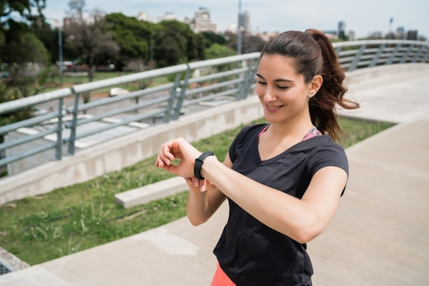 Ritratto di una donna di forma fisica che controlla il tempo sul suo orologio intelligente. sport e concetto di stile di vita sano. Foto Gratuite