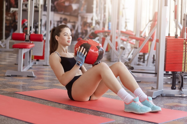 Portrait of fitness woman sitting on yoga mat holding medicine ball and doing abs exercises. close up of attractive woman in fitness wear carrying medball and looking straight ahead. Premium Photo