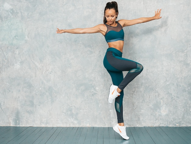 Portrait of fitness woman in sports clothing looking confident.young female wearing sportswear.beautiful model with perfect tanned body.female jumping in studio near gray wall Free Photo