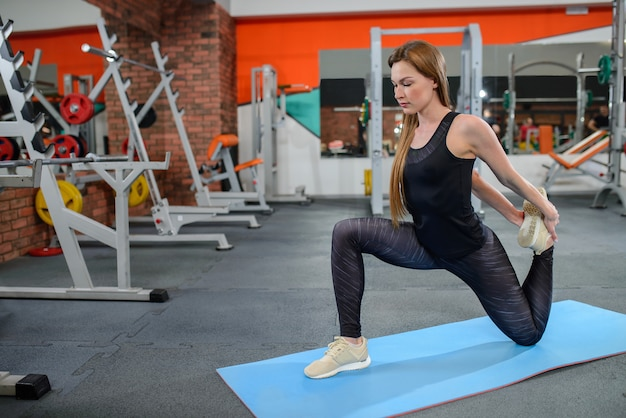Portrait of fitness woman stretching at gym before workout Premium Photo