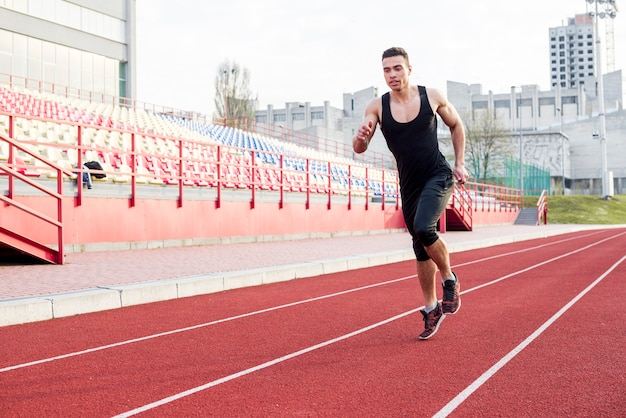 Portrait of fitness young male athlete running on race track in the stadium Free Photo