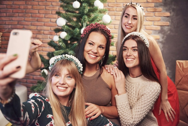 Portrait of four smiling girl with corolla on the head make selfie photo. new year's feeling. merry christmas Premium Photo