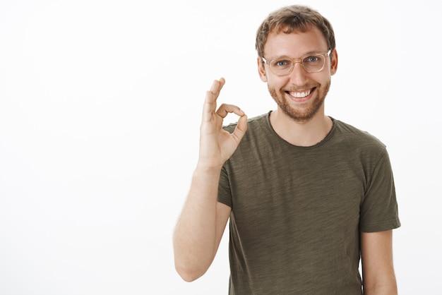 Ritratto di ragazzo europeo disponibile di bell'aspetto amichevole con gli occhiali con la barba che mostra gesto ok o ok e sorridente assicurando che l'affare del cliente sarà firmato Foto Gratuite
