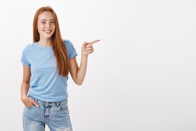 Ritratto di donna rossa carina calma e rilassata dall'aspetto amichevole con le lentiggini tenendo la mano in tasca avendo una conversazione informale e indicando a destra sorridendo gioiosamente Foto Gratuite