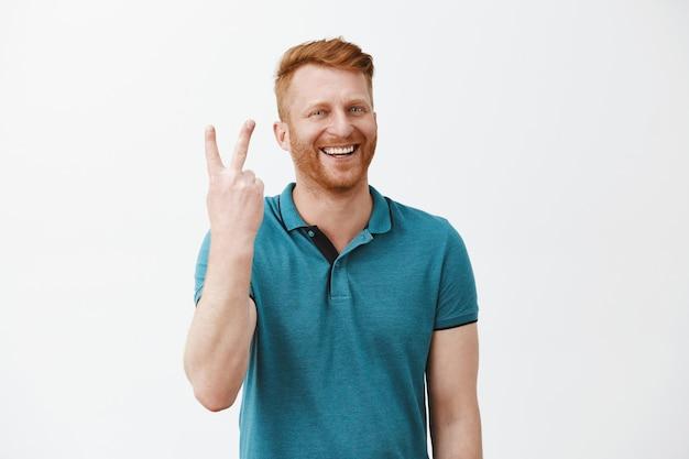 Ritratto di un maschio di redhead felice e gioioso dall'aspetto amichevole con la barba che fa segno due volte e sorride ampiamente mentre sta sopra il muro grigio Foto Gratuite