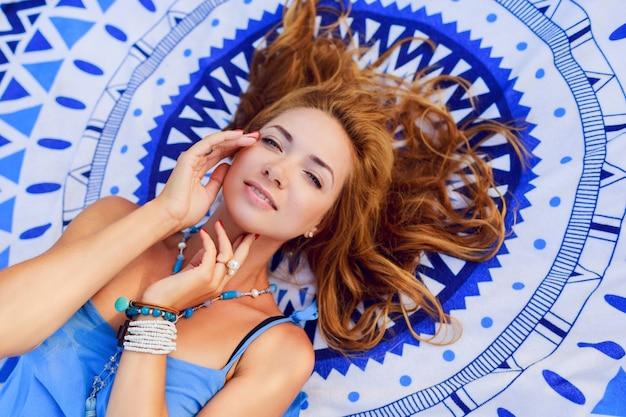 日当たりの良い夏の日にビーチタオルでリラックスした笑顔の女性の上からの肖像画。スタイリッシュな自由奔放に生きるブレスレットとネックレス。 無料写真