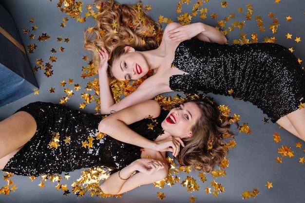 金色の見掛け倒しに横たわっている2人のファッショナブルな若い女性の上からの肖像画。豪華な黒のドレス、赤い唇、長い巻き毛、明るい気分、楽しんで、笑顔で、ゴージャスなモデル。 無料写真