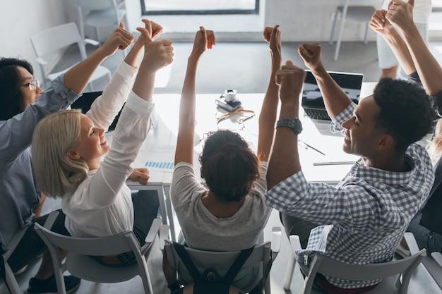 Ritratto dal retro di studenti felici seduti insieme al tavolo e alzando le mani. foto dell'interno del team di specialisti freelance che si divertono dopo un duro lavoro in ufficio. Foto Gratuite