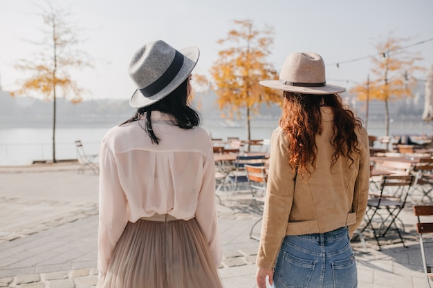自然の中で友人と話している帽子のブルネットの女性の後ろからの肖像画 無料写真