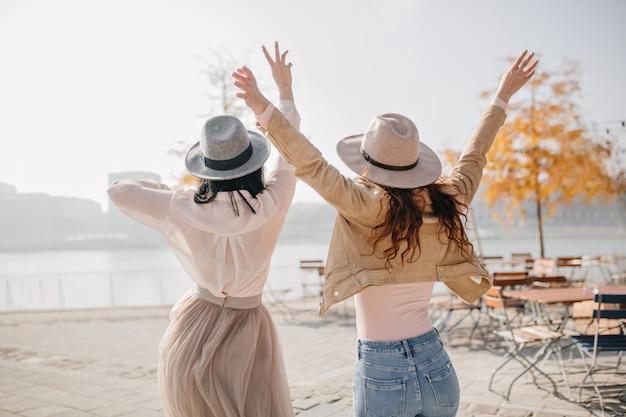 川の景色を楽しみながら前向きな感情を表現する2人の興奮した女性の後ろからの肖像画 無料写真