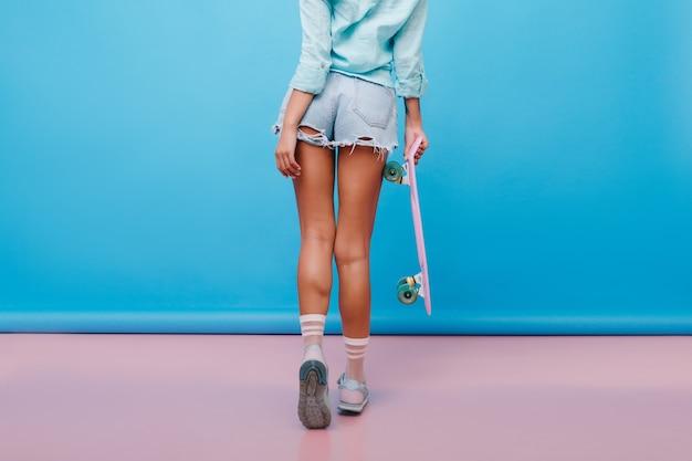 Ritratto dal retro della donna abbronzata sportiva indossa calzini carini e camicia di cotone. foto interna di una ragazza graziosa con la pelle color bronzo in pantaloncini di jeans che tiene il longboard. Foto Gratuite