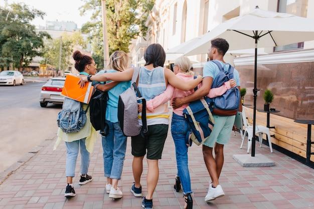 Ritratto dal retro di studenti con eleganti zaini che camminano per strada dopo le lezioni all'università. un giovane uomo alto e castano che abbraccia le ragazze mentre trascorre del tempo con loro da superare. Foto Gratuite