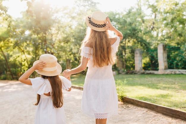 Ritratto dalla parte posteriore della figlia principale donna abbronzata alta per la strada signora bionda sottile mano nella mano con piccola ragazza bruna, camminando da prato e recinzione nel parco. Foto Gratuite