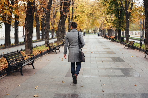 Portrait from back of young stylish guy in coat with bag strolling in city park, looking on colorful trees Free Photo