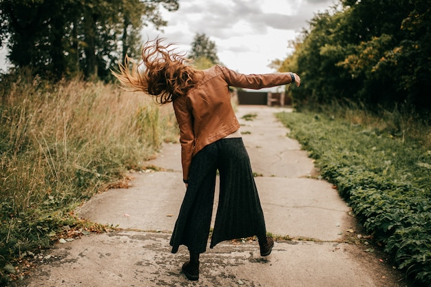 Portrait from behind of strange stylish woman walking like zombie on the road at nature Premium Photo