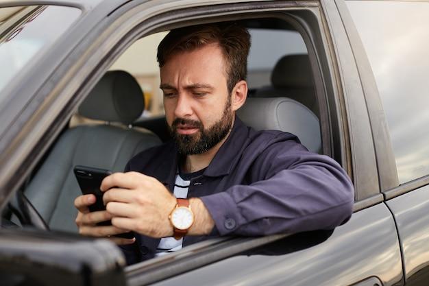 Ritratto di un uomo barbuto accigliato con una giacca blu e una maglietta a righe, seduto al volante dell'auto, chiacchierando con il collega per telefono, scontento della discussione. Foto Gratuite