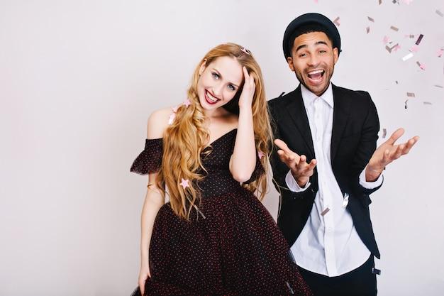 Портрет забавный праздник радостной влюбленной пары в роскошной вечерней одежде, весело проводящей время вместе. вечеринка, счастье, улыбка, выражение истинных положительных эмоций. Бесплатные Фотографии