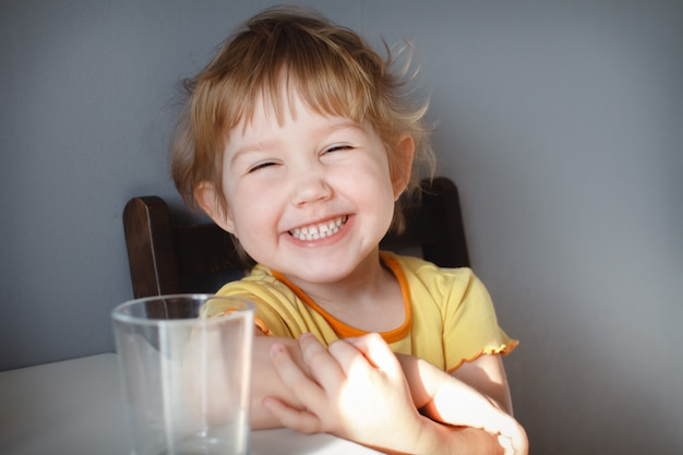 Portrait of a funny child on a gray background at the table close-up. funny antics Premium Photo