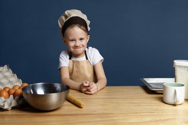 Ritratto del ragazzino sveglio divertente che indossa il grembiule beige e il cappuccio dello chef in piedi in cucina con la tazza della ciotola del metallo, il vassoio, le uova e la farina sul tavolo, pronto per fare l'impasto per la torta di pane fatta in casa o lo spazio della copia della torta Foto Gratuite