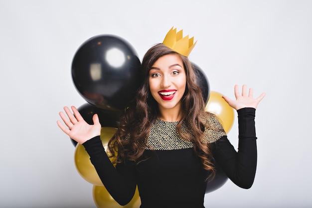 肖像画面白い金と黒の風船で新年を祝う興奮している女の子 無料写真