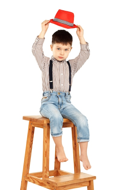 Portrait of a funny little boy sitting on a high stool in a red hat isolated on white Premium Photo